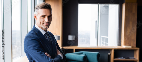 panoramic shot of smiling businessman in suit with crossed arms looking at camera in hotel