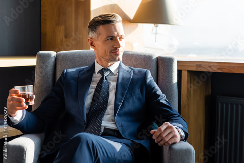 Obraz smiling businessman in suit sitting in armchair and holding glass - fototapety do salonu