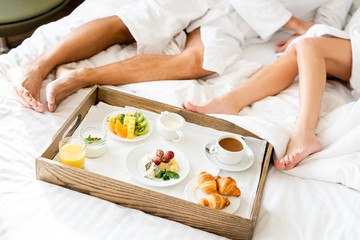 Obraz na płótnie Canvas cropped view of boyfriend and girlfriend in bathrobes sitting near tray with food