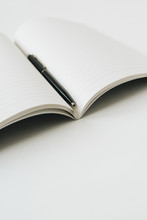 Open Notebook With Pen On Whit...