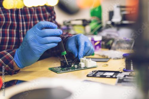 Fototapeta Technician engineer in workshop. Repairman is checking circuit board of electronic device. obraz