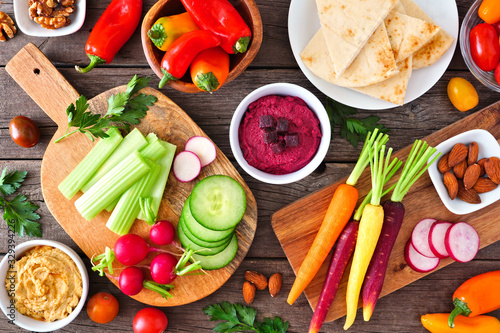 Fototapeta Table scene with a variety of fresh vegetables and hummus dips. Overhead view on a rustic wood background. obraz