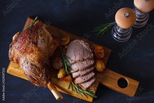 Roast leg of lamb with potatoes and rosemary on serving wooden board Canvas Print