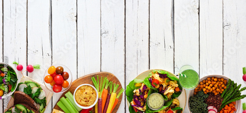 Fototapeta Healthy lunch food bottom border. Table scene with nutritious buddha bowl, lettuce wraps, sandwiches, salad and vegetables. Top view over a white wood background. Copy space. obraz