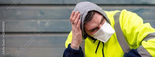 Obraz Virus mask Caucasian man wearing face protection in prevention for coronavirus. Depressed, sad male in yellow jacket, headache - fototapety do salonu