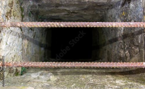 Photo Photo of an old rusty iron armature on background of ancient pit
