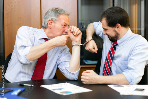 Two businessmen forced to work together bonded by handcuffs Canvas Print