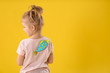 Little girl with paper fish on back against yellow background, space for text. April fool's day
