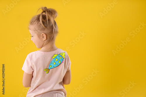 Fototapeta Little girl with paper fish on back against yellow background, space for text. April fool's day obraz