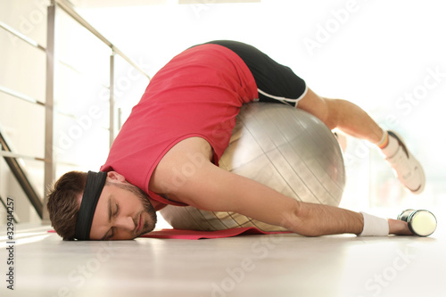Fotografie, Tablou Lazy young man with exercise ball on yoga mat indoors
