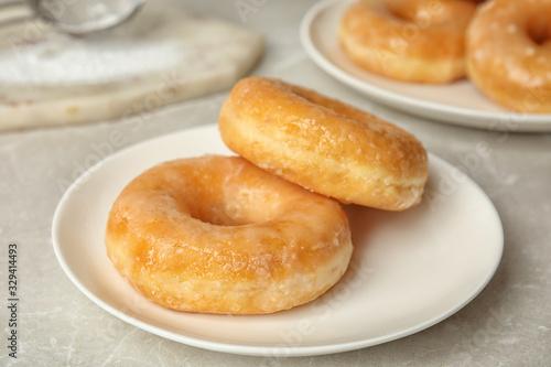 Fototapeta Sweet delicious glazed donuts on light table obraz
