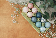 Easter Eggs Natural Dye In Carton Tray On Rustic Table With Flowers, Flat Lay. Modern Pastel Pink And Blue Easter Eggs Painted With Organic Beets, Red Cabbage, Carcade Tea. Zero Waste Holiday
