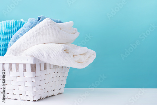 Valokuva stack of clean towels in a white laundry basket on blue background
