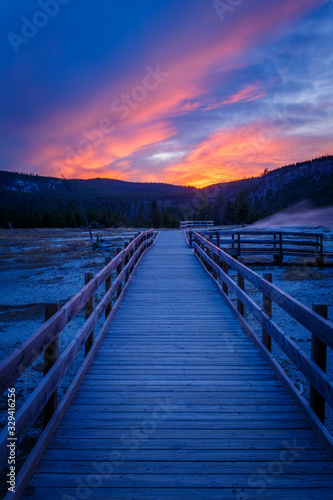 Fotografía Biscuit basin walkway with blue steamy water and beautiful colorful sunset