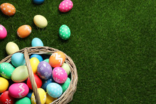 Colorful Easter Eggs In Basket On Green Grass, Above View. Space For Text