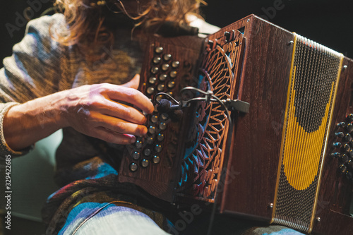 Photo Accordionist playing accordion on stage closeup