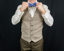 Portriat Of Dapper Man In Vest Straightening A Purple Bow Tie. Eccentric Style. Nerd With Bow Tie. Getting Dressed For Party. Copy Space.