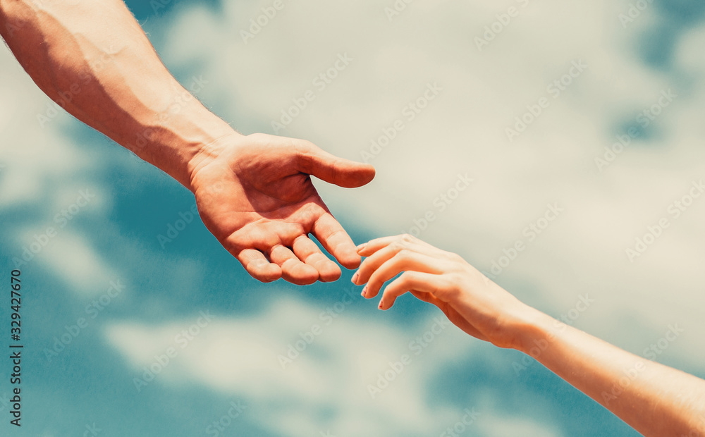 Fototapeta Giving a helping hand. Lending a helping hand. Hands of man and woman reaching to each other, support. Hands of man and woman on blue sky background