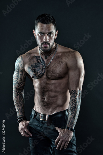 Be strong. muscular bodybuilder with body tattoo. athletic male show abdominal muscles. fitness model topless. healthcare lifestyle. body strong abs. Wild masculine beauty. macho. brutal and sexy