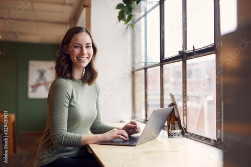 Fototapeta Beautyful young woman is sitting on a café trying to study obraz