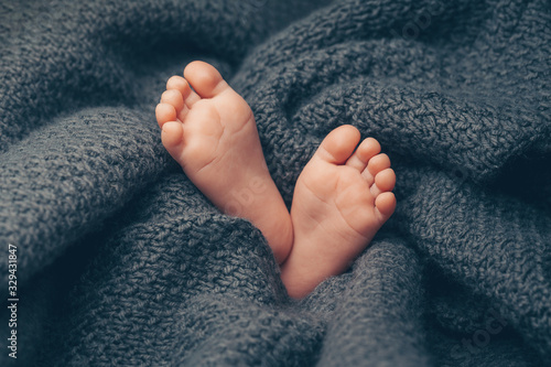 Photo Soft newborn baby feet against a dark grey blanket, closeup.