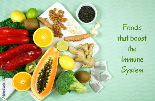 fototapeta na drzwi i meble Foods that boost the Immune System. Citrus, red bell peppers, broccoli, garlic, ginger, spinach, almonds, turmeric, green tea, papaya, kiwi fruit, poultry and sunflower seeds. Text title heading.