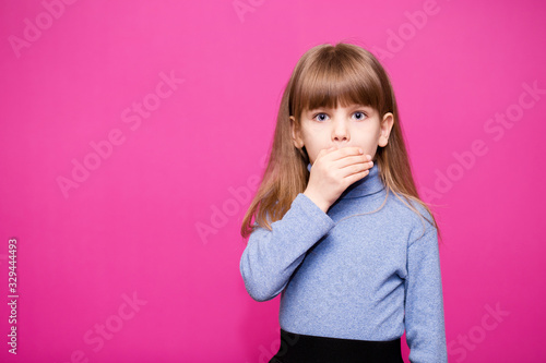 Obraz Cute little girl covering her mouth showing intense expression of fear isolated on pink background - fototapety do salonu