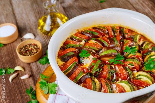 Fototapeta Stewed vegetable ratatouille with mozzarella cheese in white oven pan. obraz