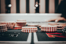 Casino Concept Background. Poker Chips On The Table. A Gaming Table In A Luxury Casino. Casino Symbols Composition. Roulette Wheel, Poker Chips, Dice, Cards. Recreation And Entertainment Concept.