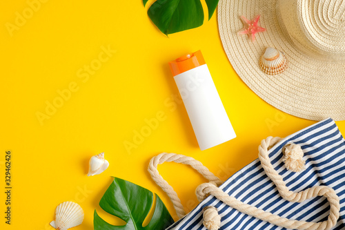 Top view suntan cream bottle, beach bag, female hat and tropical leaves on yellow background. Sun protection on summer vacation concept