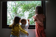 Leinwandbild Motiv three asian little child seeing out of the window glass when standing in the bedroom
