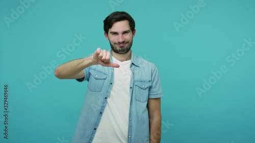 Fotografie, Obraz Dislike to you! Bearded guy in jeans shirt pointing to camera and showing thumbs down, looking dissatisfied upset about choice, making disapproval sign
