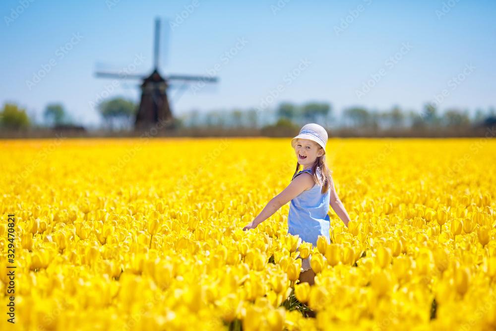 Fototapeta Kids in tulip flower field. Windmill in Holland