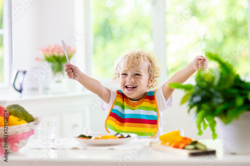 Baby eating vegetables. Solid food for infant. Wallpaper Mural