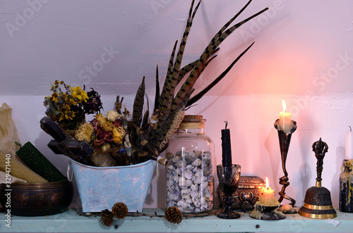 Foto Witch altar with burning candles, dry herbs and feathers.