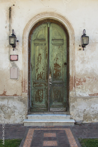 Puerta de madera antigua de color verde que pertenece a una casa rural en un pue Wallpaper Mural