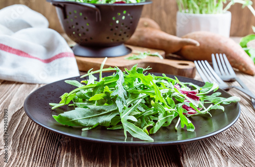 Photo Fresh organic arugula leaves on black plate