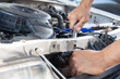 The mechanic used a wrench to remove the spark plug from a car. Mechanic inspect and repair the damaged car.