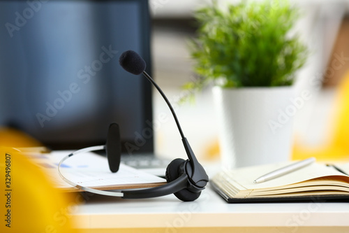 Fototapeta Empty remote office workplace with laptop pc and headset closeup