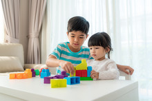 Asian Cute Brother And Sister Play With A Toy Block Designer On The Table In Living Room At Home. Concept Of Bonding Of Sibling, Friendship And Learn Through Play Activity For Kid Development.