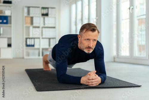 Fototapeta Athletic man doing plank exercises in a gym obraz