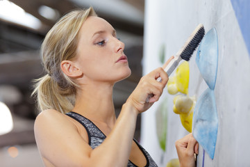 woman using brush to clean grip on indoor climbing wall