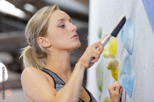 obraz PCV woman using brush to clean grip on indoor climbing wall
