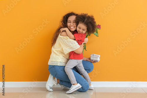 Obraz Little African-American girl greeting her mother near color wall - fototapety do salonu