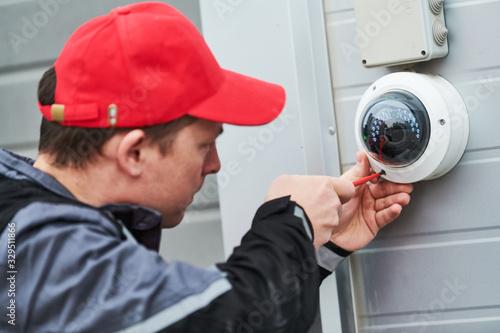 Obraz video surveillance service. Technician installing camera - fototapety do salonu