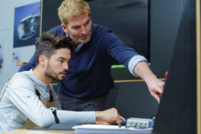 Tutor Helping Student Technician Using Computer