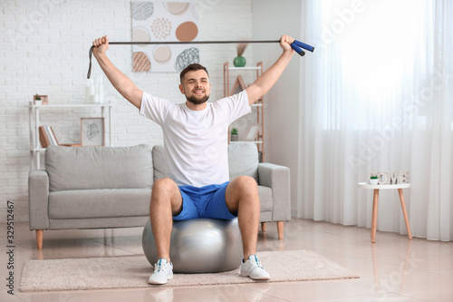 fototapeta na drzwi i meble Sporty young man training at home