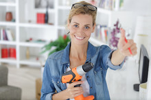 Beautiful Young Woman At Home With Drill Showing Thumbs Up