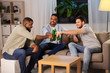 friendship, leisure and people concept - happy male friends drinking beer at home at night