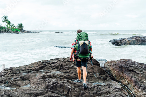 Digital nomad man on the beach with backpack Wallpaper Mural